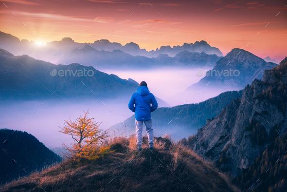 Man on the mountain peak looking on mountain valley - Stock Photo - Images