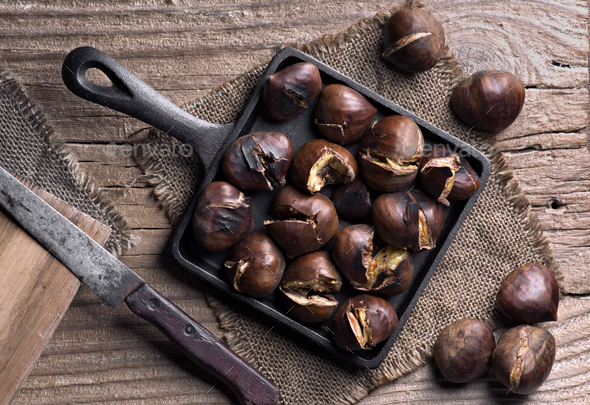 pan full of roasted chestnuts on rustic wood - Stock Photo - Images