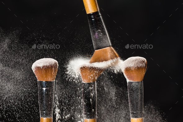 Make up, beauty and mineral powder concept - Cosmetics brush and explosion colorful makeup powder - Stock Photo - Images