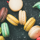 Sweet colorful French macaroon cookies over black background, top view - PhotoDune Item for Sale