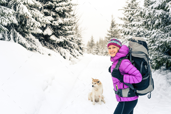 Happy girl hiking in winter forest with dog - Stock Photo - Images