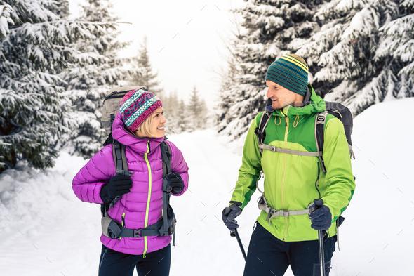 Couple hikers trekking in winter woods - Stock Photo - Images