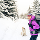 Happy girl hiking in winter forest with dog - PhotoDune Item for Sale