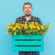 Free Download Cheerful handsome man florist holding box of tulips on blue background Nulled