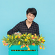 Free Download Happy middle-aged woman florist wearing glasses with box of tulips on blue background Nulled
