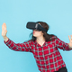 Free Download Technology and people concept - Young woman testing vr-glasses with hands up on blue background. Nulled
