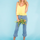 Free Download Beautiful blonde young woman standing with bouquet of yellow tulips on blue background. Nulled