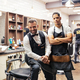 Two male haidressers and hairstylists sitting in barber shop. - PhotoDune Item for Sale