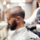 Hipster man client visiting haidresser and hairstylist in barber shop. - PhotoDune Item for Sale
