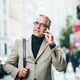 Mature businessman standing on a street in city, using smartphone. - PhotoDune Item for Sale
