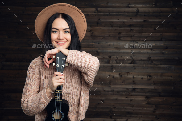 Portrait of a smiling casual woman posing with guitar against wooden plank - Stock Photo - Images