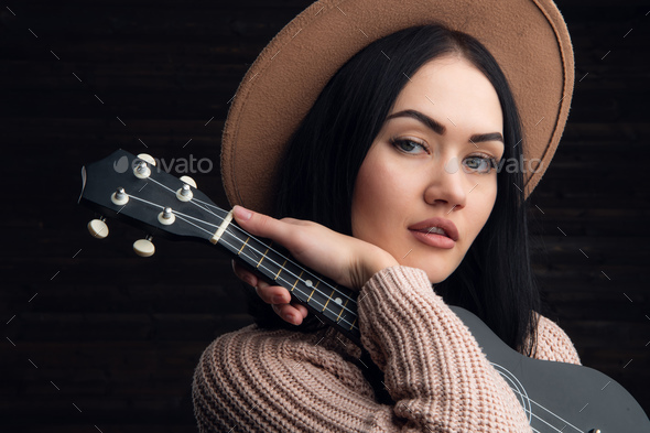 Close up portrait of young caucasian woman playing ukulele in front of a wooden background. Studio - Stock Photo - Images