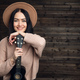 Portrait of a smiling casual woman posing with guitar against wooden plank - PhotoDune Item for Sale