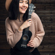 Young smiling girl with a ukulele sit in studio on a wooden background - PhotoDune Item for Sale