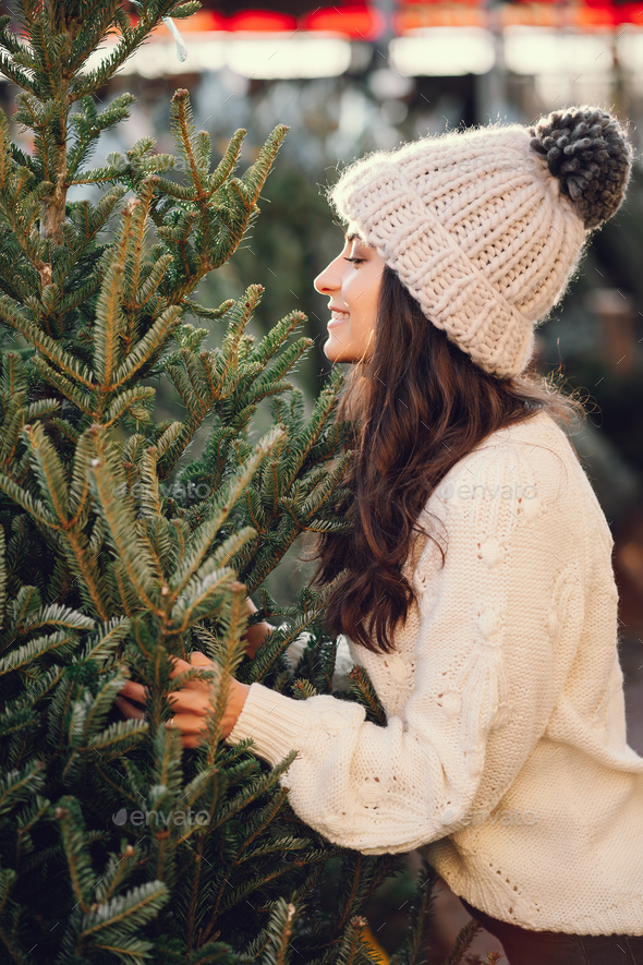 Cute brunette in a white sweater with Christmas tree - Stock Photo - Images