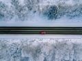 Aerial view of country road going through the beautiful snow covered landscape. - PhotoDune Item for Sale