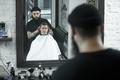Children hairdresser cutting little boy against a dark background. - PhotoDune Item for Sale