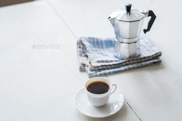 Cup of coffee, coffee kettle on a white table - Stock Photo - Images