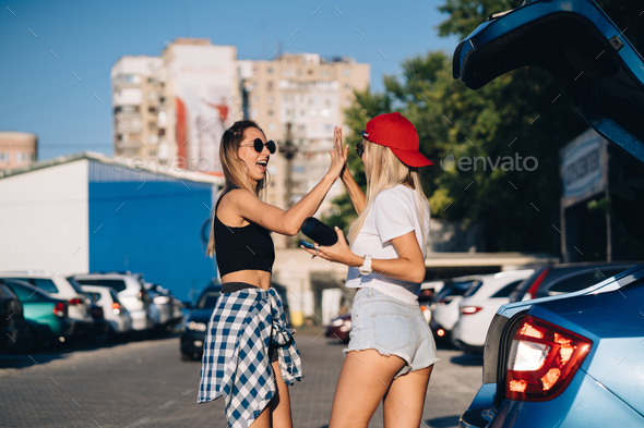 Two young girls in sunglasses posing for the camera on the car parking - Stock Photo - Images