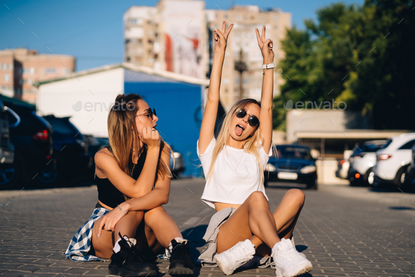 Two young, sexy girls are sitting on the ground - Stock Photo - Images