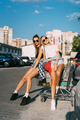 Two young girls in sunglasses posing for the camera on the car parking - PhotoDune Item for Sale