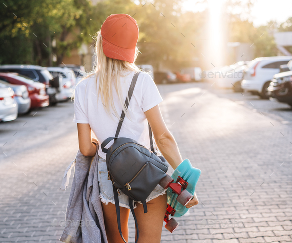Young girl with a skateboard on a car park - Stock Photo - Images