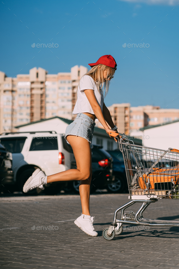 Young, sexy girl posing with a basket in a car park - Stock Photo - Images