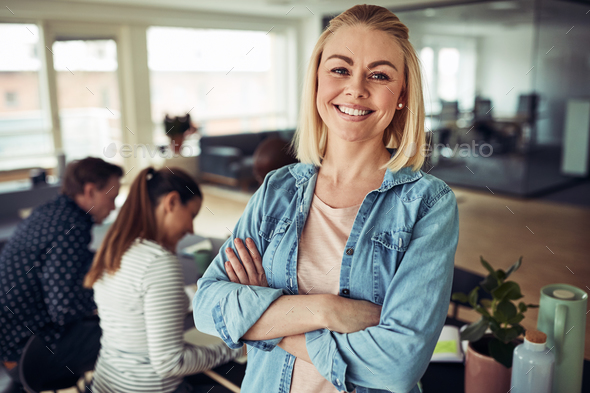 Smiling young businesswoman with colleagues working in the background - Stock Photo - Images