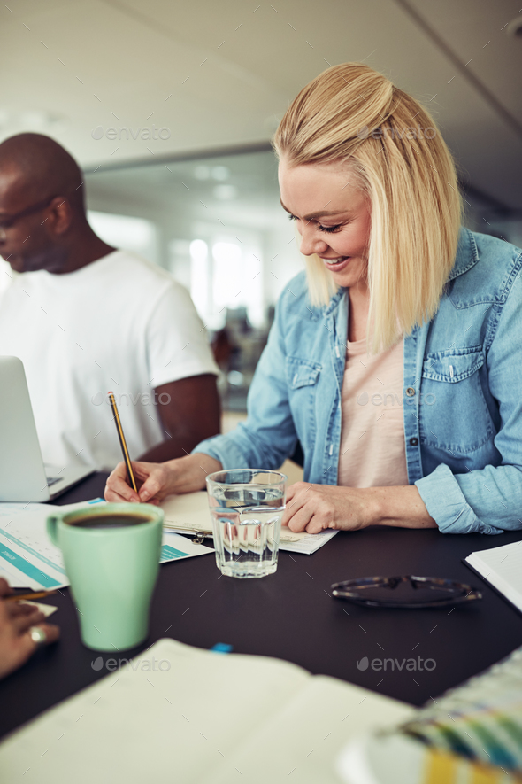 Smiling businesswoman working with a colleague at an office table - Stock Photo - Images