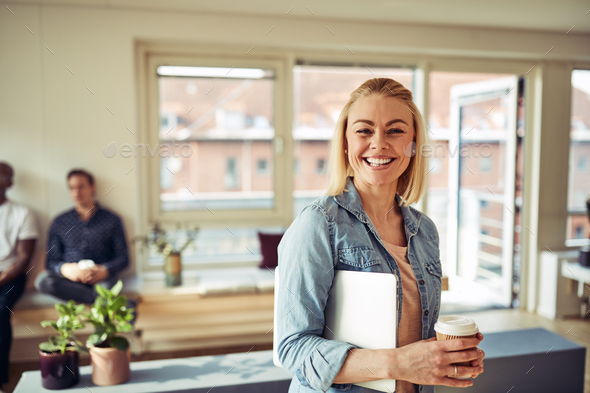 Smiling young businesswoman standing in an office during her break - Stock Photo - Images
