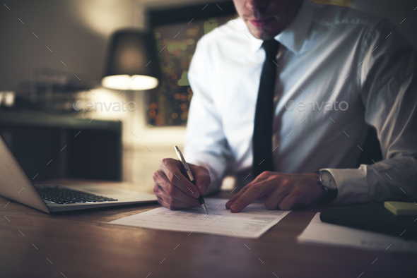 Serious businessman signing contract at office - Stock Photo - Images