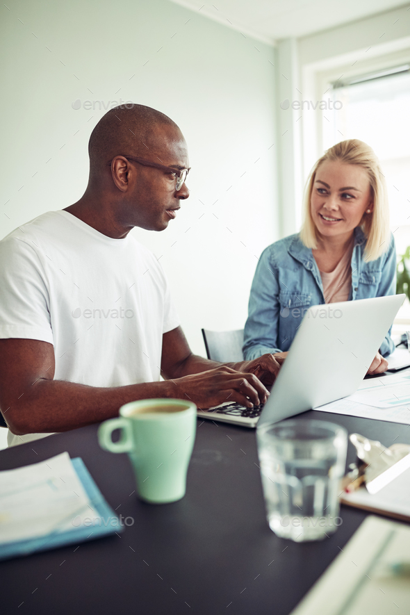 Two diverse office colleagues using a laptop and talking together - Stock Photo - Images