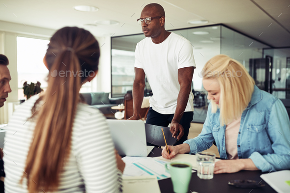 African businessman talking with colleagues around an office table - Stock Photo - Images