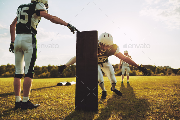 American football players doing tackling drills on a football field - Stock Photo - Images