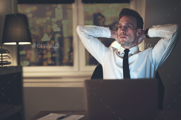 Businessman thinking at office working overtime - Stock Photo - Images