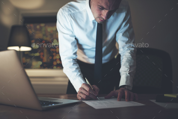 Serious businessman signing contract - Stock Photo - Images