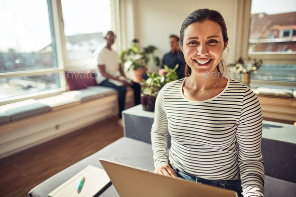 Smiling businesswoman using a laptop with coworkers in the background - Stock Photo - Images