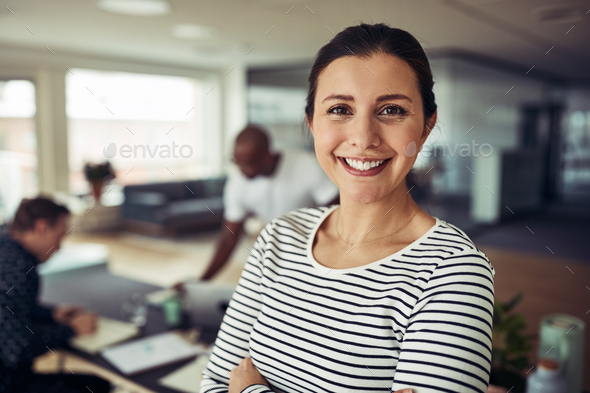 Smiling young businesswoman at work with colleagues in the background - Stock Photo - Images