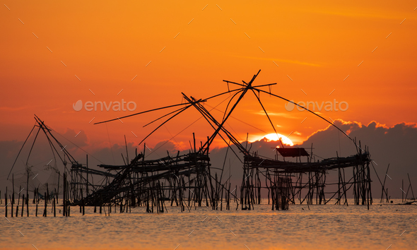Sunrise with traditional fishing trap in Pak Pra village, Phatthalung, Thailand - Stock Photo - Images