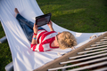 woman using a tablet computer while relaxing on hammock - PhotoDune Item for Sale