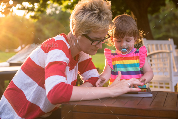 mom and her little daughter using tablet computer - Stock Photo - Images