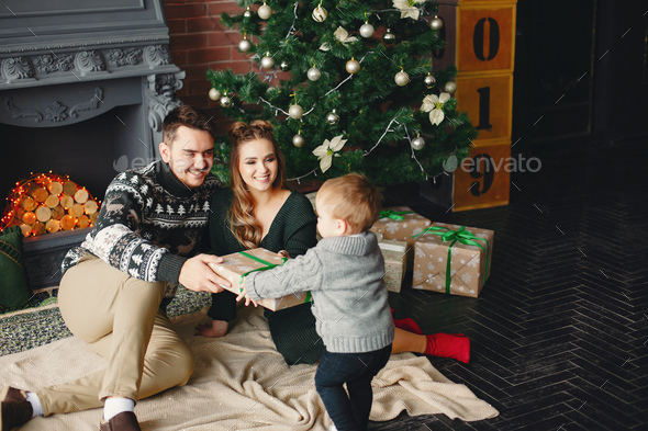 Cute family sitting near Christmas tree - Stock Photo - Images