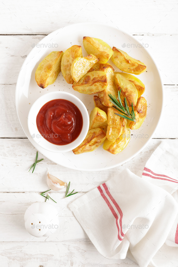 Potato baked and tomato ketchup on white plate, wooden background, top view - Stock Photo - Images