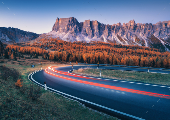 Blurred car headlights on winding road in mountains at dusk - Stock Photo - Images