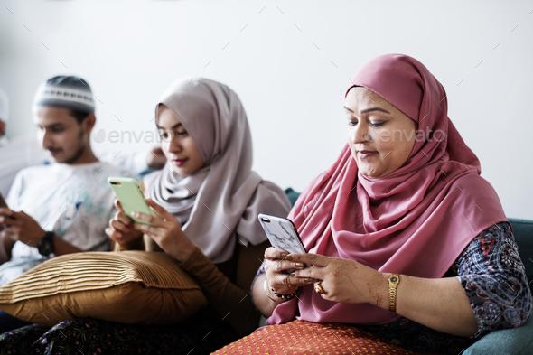 Muslim friends using social media on phones - Stock Photo - Images