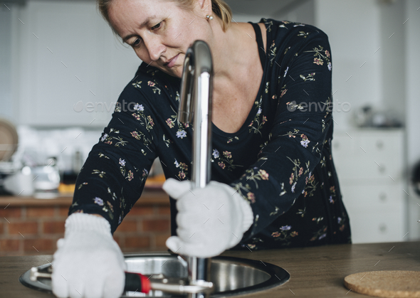 Handy woman fixing the faucet - Stock Photo - Images