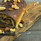Poppy seed cake with raisins and nuts on an old chopping board - PhotoDune Item for Sale
