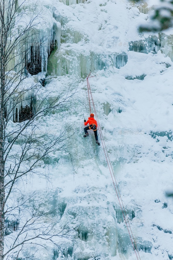 Athletic man in climbing a large blue wall of ice in Finland - Stock Photo - Images
