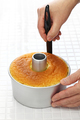 homemade orange chiffon cake cooking, using a knife to separate the cake from the pan - PhotoDune Item for Sale