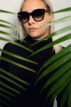 Close-up of woman with sunglasses hiding behind tropical palm leaves - PhotoDune Item for Sale